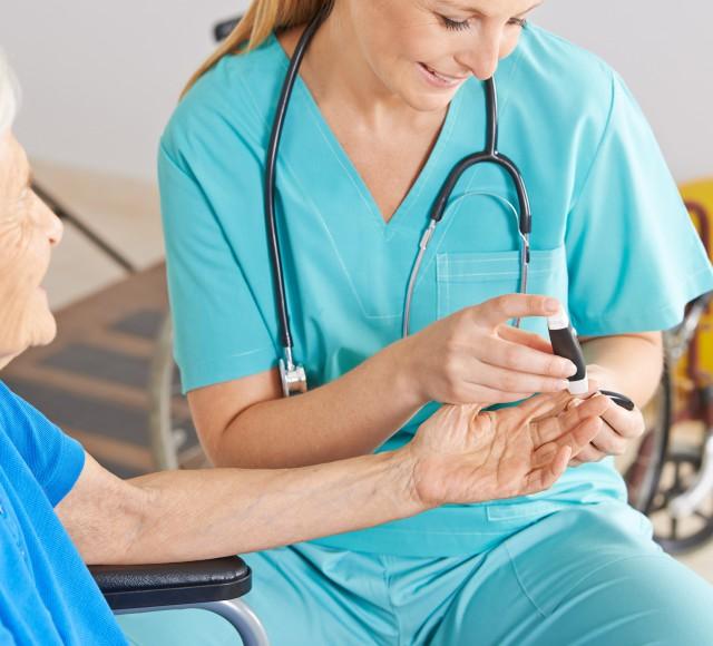 Altenpflegerin beim Messen vom Blutzucker bei einer Seniorin im Pflegeheim